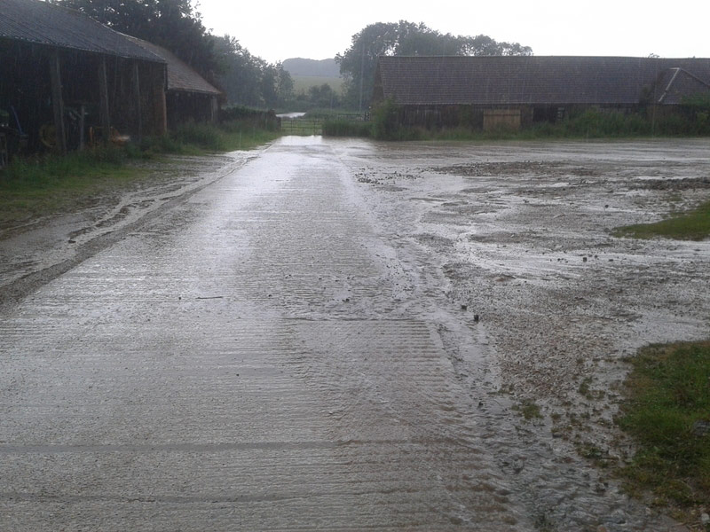 Water running through a farmyard towards wetlands (visible in the background). This photo was also taken during a relatively extreme rain event